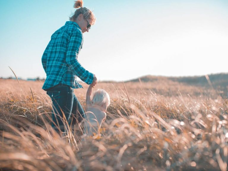 Woman taking care of her daughter walking through a field
